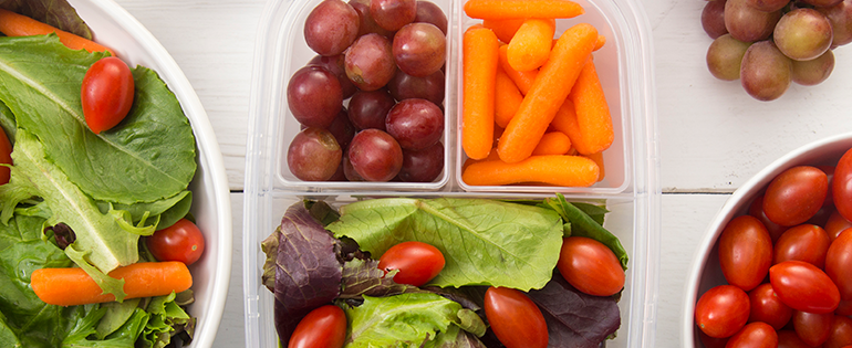 packed lunch with salad, carrots and grapes