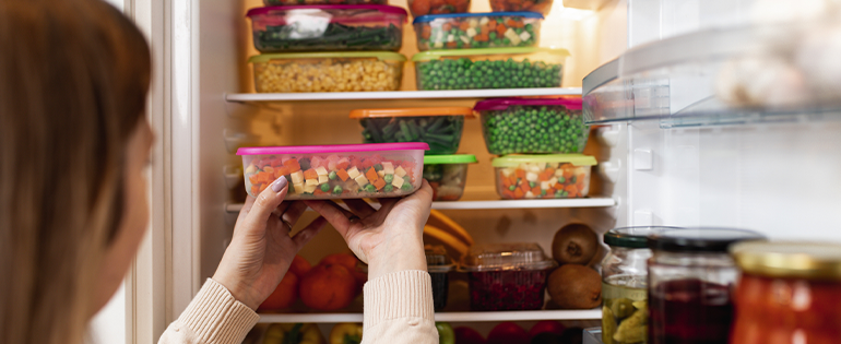 Woman Putting Meal Prep Containers in Fridge