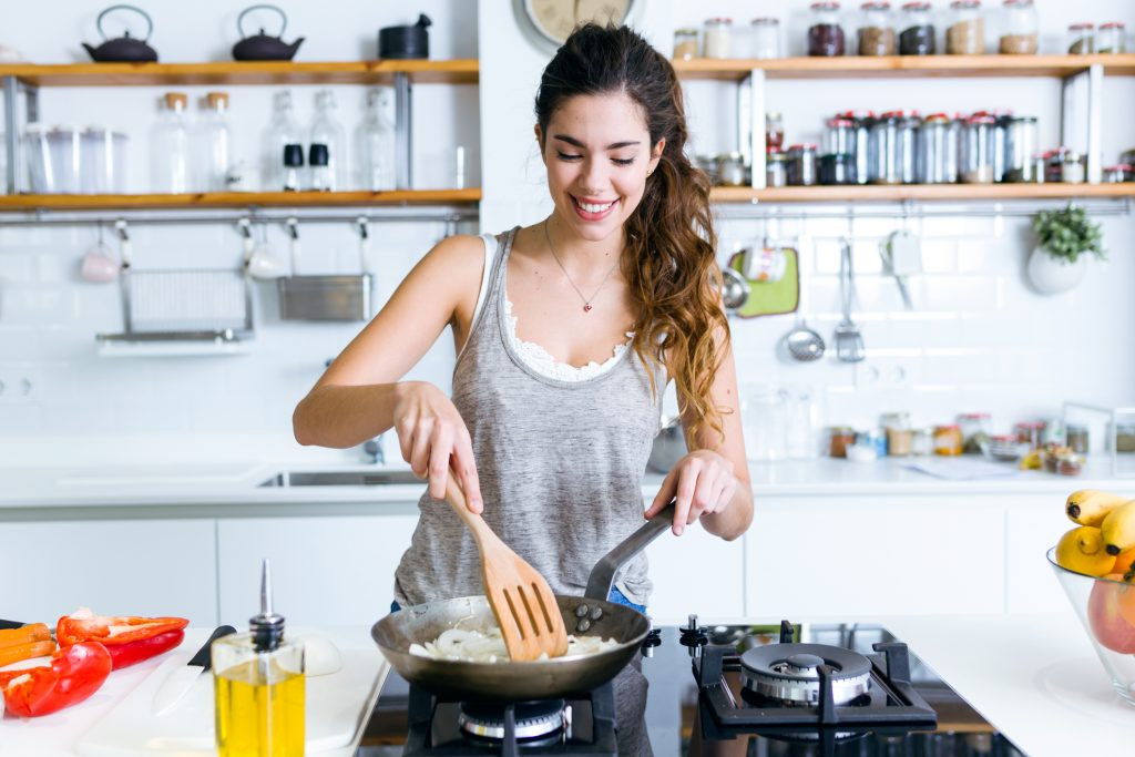 ortrait of young woman frying onion into the pan in the kitchen.
